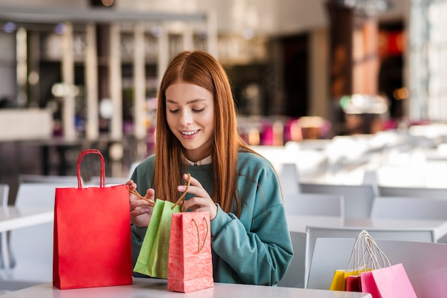 Mulher ruiva olhando para sacolas de compras