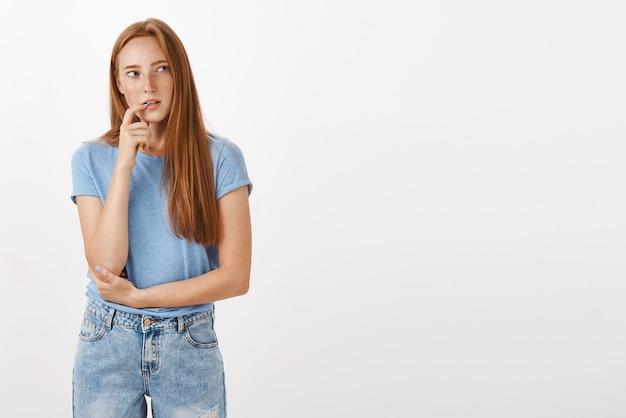 Mulher ruiva pensativa, concentrada e curiosa de camiseta azul e jeans, mordendo o dedo, intrigada, olhando para a direita enquanto pensa, tem desejo ou interesse por algo
