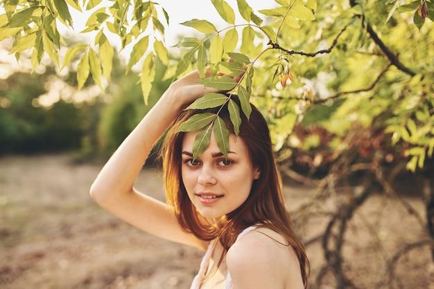 Mulher ruiva perto de uma árvore com folhas verdes