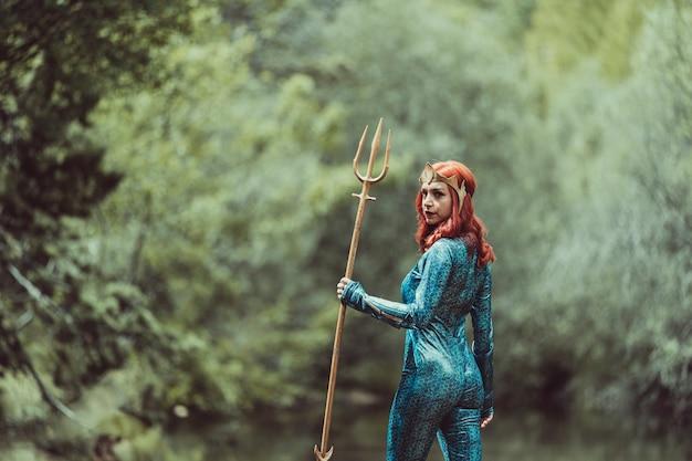 Mulher ruiva posando com fantasia de super-herói