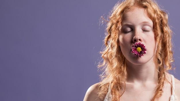 Mulher ruiva posando com uma flor na boca e cópia espaço