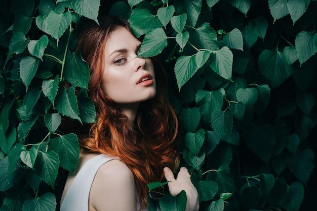 Mulher ruiva posando entre folhas verdes