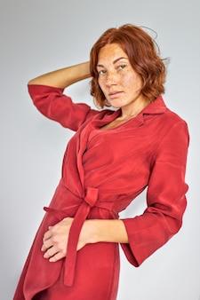Mulher ruiva posando, linda senhora de vestido sério olha para a câmera, tendo um olhar encantador. fundo de estúdio isolado