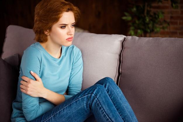 Mulher ruiva posando no sofá em casa