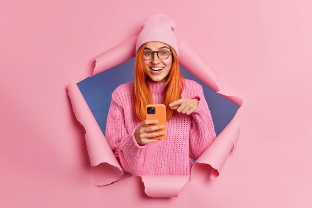Mulher ruiva positiva aponta para a tela do smartphone moderno obtém informações úteis de surfistas na internet em risos de redes sociais positivamente usa aplicativo móvel ou nova tecnologia. estilo de vida do blogger.