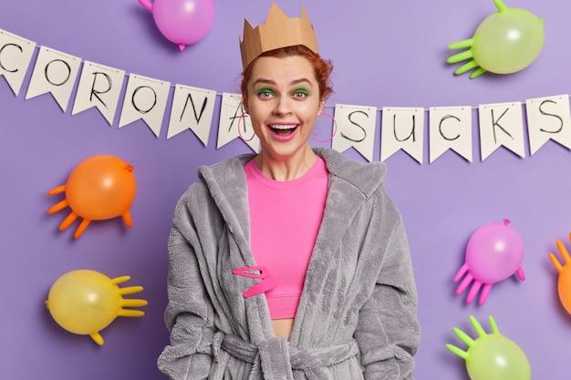 Mulher ruiva positiva com maquiagem brilhante fica feliz na frente e usa roupas domésticas e passa seu tempo livre em poses de festa contra uma parede decorada