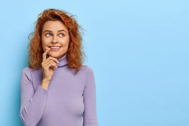 Mulher ruiva positiva imagina momento agradável com namorado, sorri gentilmente, olha para cima com rosto sonhador, tem cabelo ruivo curto, veste suéter roxo, isolada em parede azul, espaço em branco para texto
