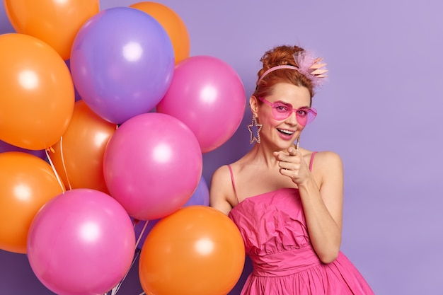 Mulher ruiva positiva indica quando você convida para festa e celebração usa óculos escuros da moda e vestido segura um monte de balões inflados comemora aniversário