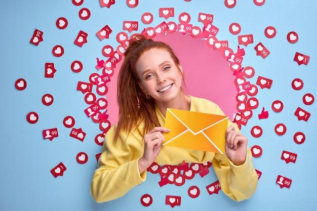 Mulher ruiva positiva segurando uma carta em forma de mensagem e sorrindo na parede azul