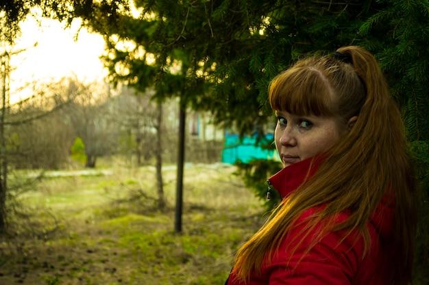 Mulher ruiva respira ar puro na natureza floresta parque ao ar livre fresco conceito de estilo de vida saudável