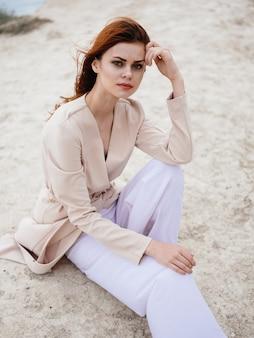 Mulher ruiva romântica com um suéter leve na natureza ao ar livre