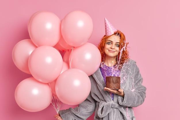 Mulher ruiva satisfeita segurando bolo de chocolate comemora aniversário se divertindo na festa vestida com roupas casuais segurando um monte de balões de ar inflados rosa tem expressão alegre