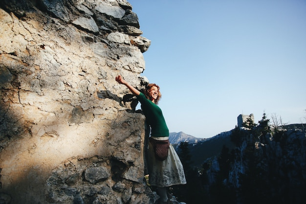 Mulher ruiva se inclina para a rocha e olha para o sol