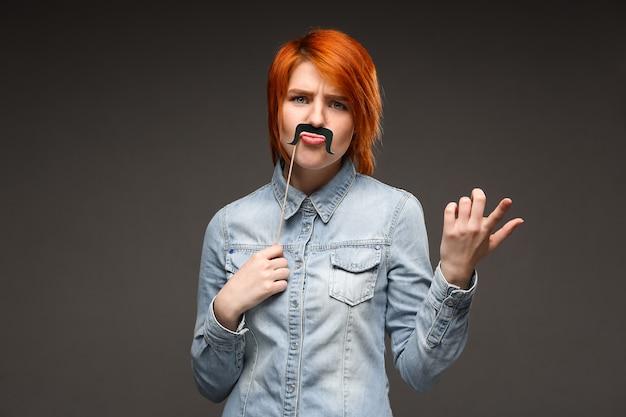 Mulher ruiva segurando bigode falso fazendo careta