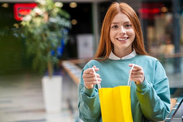 Mulher ruiva segurando sacola amarela