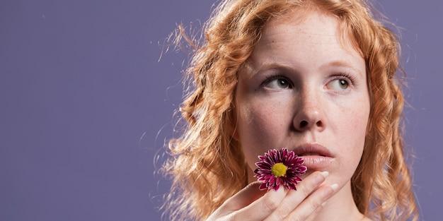 Mulher ruiva segurando uma flor perto da boca com espaço de cópia