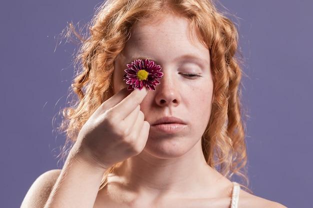 Mulher ruiva segurando uma flor sobre o olho dela