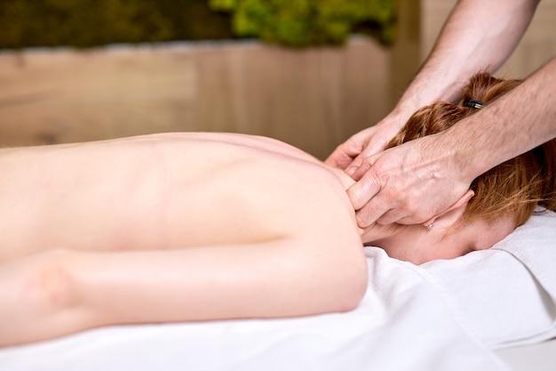 Mulher ruiva sem camisa fazendo massagem nas costas e ombros deitada de bruços