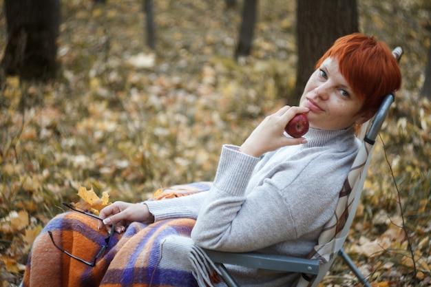 Mulher ruiva sentada em uma espreguiçadeira dobrável em um fundo de floresta outono