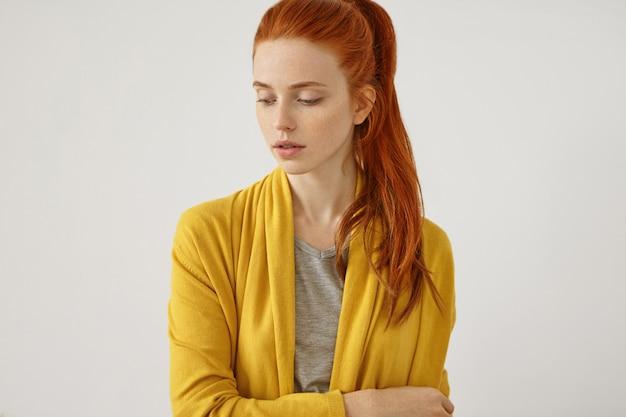 Mulher ruiva séria com pele sardenta sem maquiagem, vestindo capa amarela, em pé de mãos cruzadas. mulher bonita com rabo de cavalo avermelhado, olhando para baixo