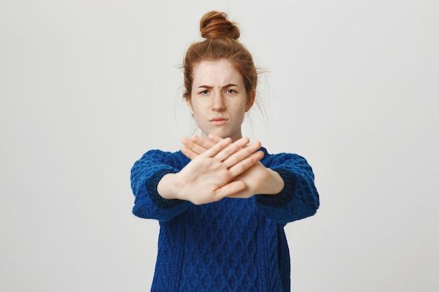 Mulher ruiva séria estende a mão para mostrar, parar, restringir ou proibir