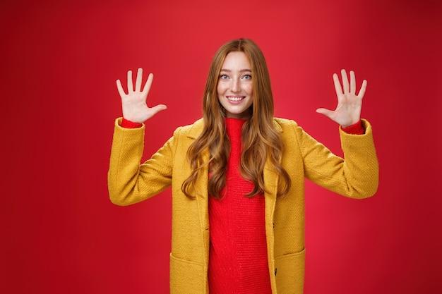 Mulher ruiva simpática bonita e meiga com olhos azuis e sardas no elegante casaco amarelo, mostrando o número dez ou ordenando uma dúzia de coisas enquanto sorri alegremente para a câmera sobre fundo vermelho.