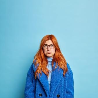Mulher ruiva sombria descontente franze os lábios e olha tristemente acima da posição descontente usa casaco azul de pele.
