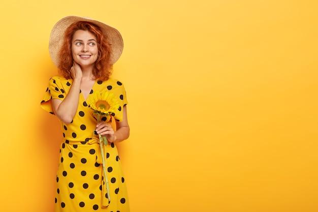 Mulher ruiva sonhadora posando com vestido polca amarelo e chapéu de palha