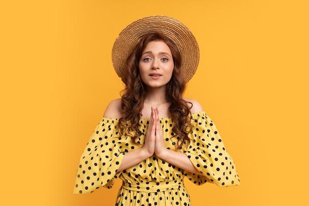 Mulher ruiva sonhadora posando em um vestido amarelo com mangas amarelas. clima de verão.