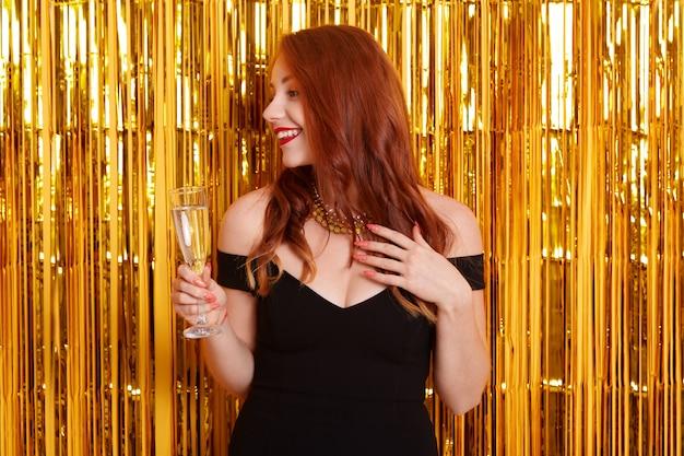 Mulher ruiva sorridente com copo de vinho olhando para o lado, vestido preto com ombros nus, encostado na parede com enfeites dourados
