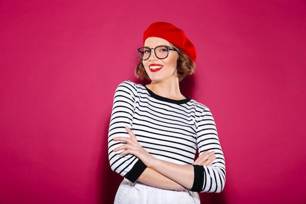 Mulher ruiva sorridente em óculos posando com braços cruzados e olhando para a câmera sobre rosa