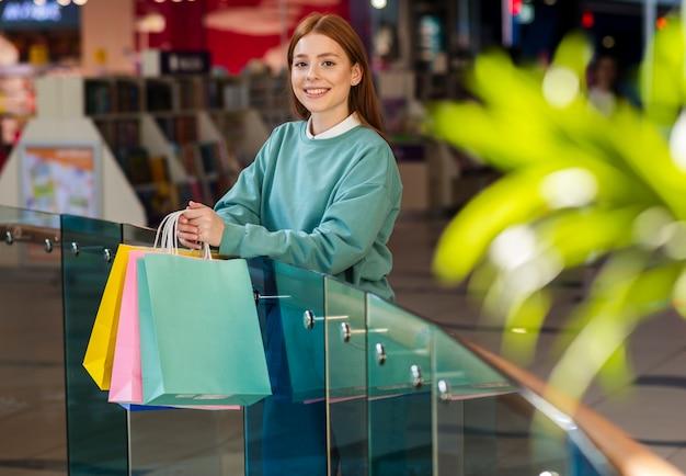 Mulher ruiva sorridente segurando sacolas de compras