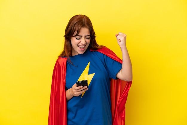 Mulher ruiva super-heroína isolada em fundo amarelo com o telefone em posição de vitória