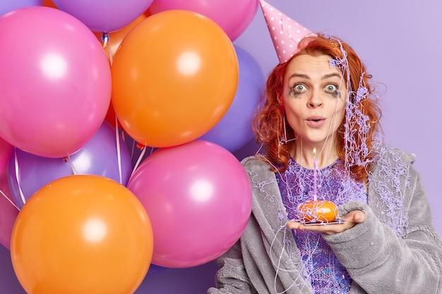 Mulher ruiva surpresa com maquiagem estragada após comemorar aniversário e olha chocada na frente segurando bolinho e balões inflados coloridos isolados na parede roxa