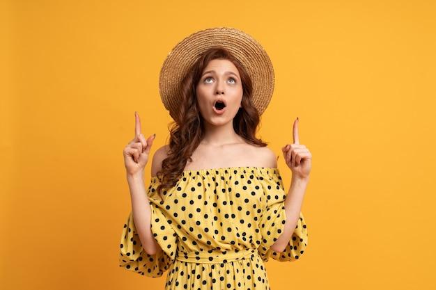 Mulher ruiva surpresa posando em um vestido amarelo com mangas apontando para cima por dedos em amarelo. clima de verão.