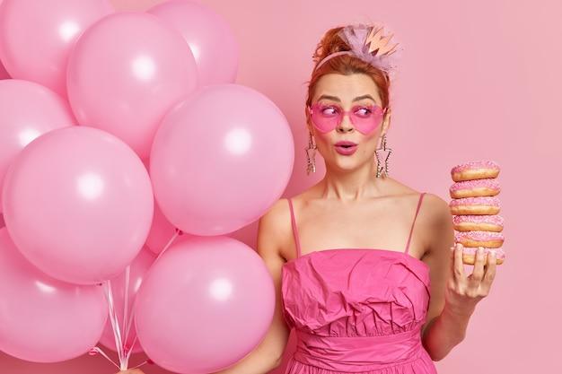 Mulher ruiva surpresa segurando rosquinhas saborosas, comemorando aniversário, expressão maravilhada