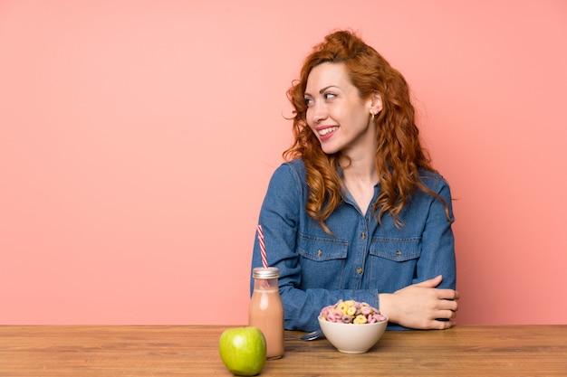Mulher ruiva, tendo cereais de pequeno-almoço e frutas em pé e olhando para o lado