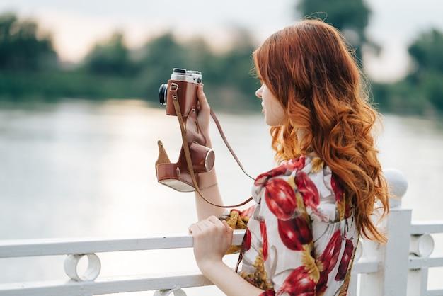 Mulher ruiva tirando fotos ao ar livre