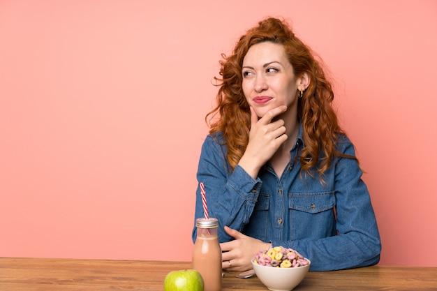 Mulher ruiva tomando café da manhã cereais e frutas pensando uma idéia