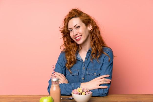 Mulher ruiva tomando café da manhã cereais e frutas rindo