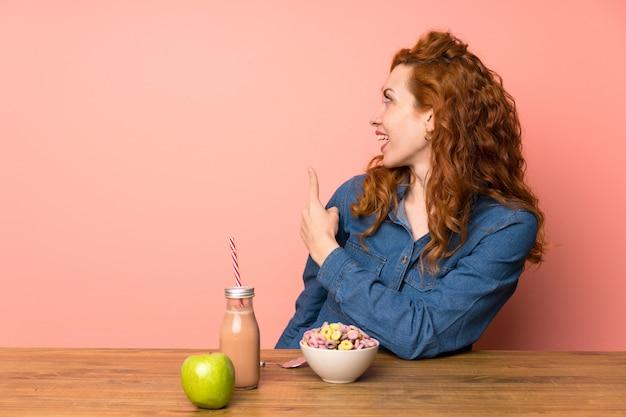 Mulher ruiva tomando cereais e frutas, apontando para trás com o dedo indicador