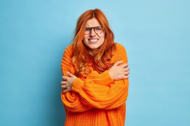 Mulher ruiva treme de abraços de frio para aquecer passeios ao ar livre durante a temperatura congelante cerra os dentes e treme usa apenas um suéter.