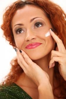 Mulher ruiva usando creme facial