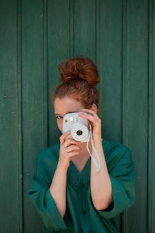Mulher ruiva usando uma câmera vintage