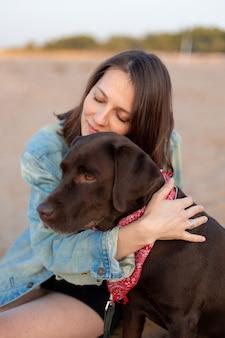 Mulher rural europeia feliz com cabelo escuro em uma jaqueta jeans vintage abraçando um cachorro e sorrindo
