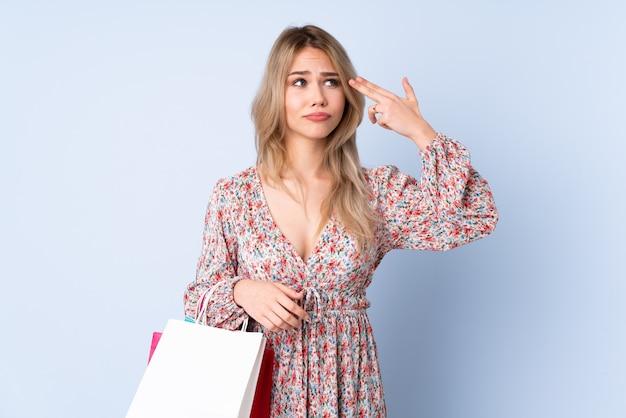 Mulher russa adolescente com sacola de compras isolada na parede azul com problemas fazendo o gesto de suicídio