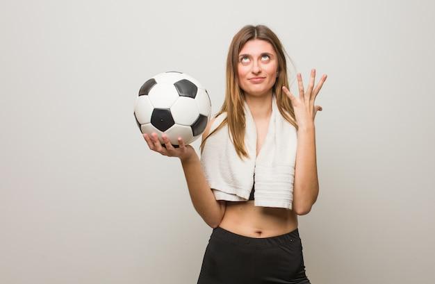 Mulher russa de aptidão jovem muito e com medo. segurando uma bola de futebol.