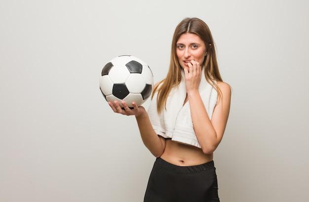 Mulher russa de aptidão jovem roer unhas, nervoso e muito ansioso. segurando uma bola de futebol.