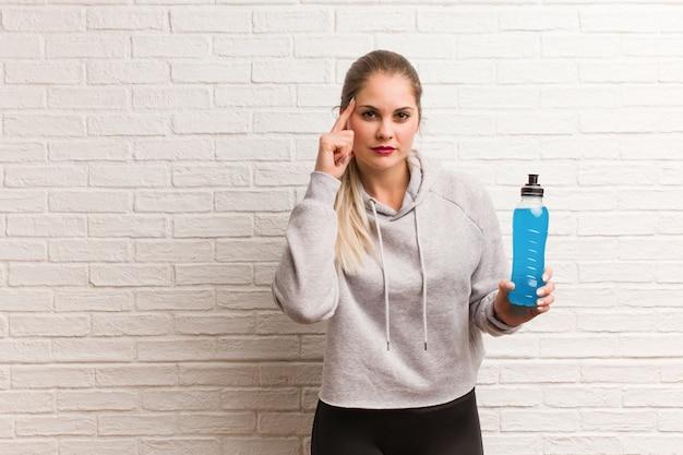 Mulher russa de aptidão jovem segurando uma bebida energética