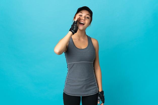 Mulher russa de esporte isolada em azul gritando com a boca bem aberta
